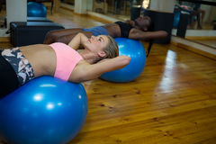 Two fit women performing pilate on exercise ball Royalty Free Stock Image