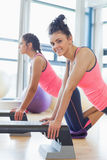 Two fit women performing step aerobics exercise Royalty Free Stock Photo