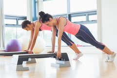 Two fit women performing step aerobics exercise in gym Royalty Free Stock Photos