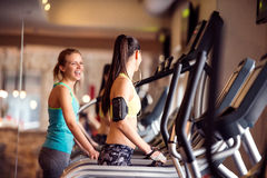 Two fit women running on treadmills in modern gym. Two attractive fit women running in sports clothes on treadmills in modern gym Royalty Free Stock Photo