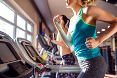 Two fit women running on treadmills in modern gym Royalty Free Stock Photography