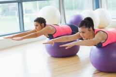 Two fit women stretching out hands on fitness balls in gym Stock Photos