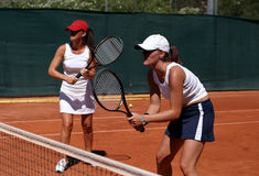 Two fit, young, healthy women playing doubles at tennis in the sun stock photo