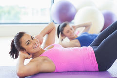 Two fit young women doing pilate exercises Royalty Free Stock Image