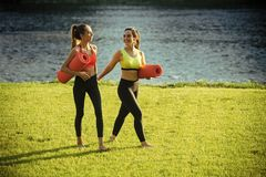 Two fitness girl with yoga mat outdoor in nature. Fit women with exercise accessory in summertime landscape stock photography
