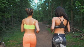 Two fitness girls running through the woods. They practice sport life style. For the health and tone. Back view stock video footage