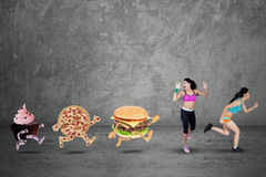Two Fitness Woman Chased by Junk Food Royalty Free Stock Photos