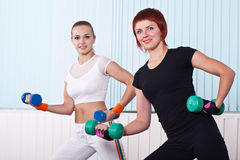 Two fitness women lifting dumbbells Stock Image