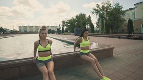 Two fitness women in sports clothing doing triceps exercise outdoors in morning. Two fitness women with tattoo in sports clothing doing triceps exercise outdoors stock video