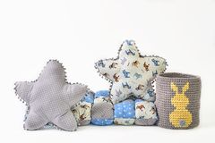 Two five-pointed star shaped pillows, patchwork comforter and knitted padded stool on white background. Two five-pointed star shaped pillows, patchwork Royalty Free Stock Image
