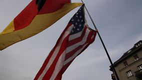 Two flags. American and German waving on the pole stock footage
