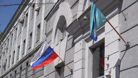 Two flags,fluttering from the hotel building.  stock footage
