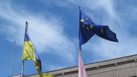 Two flags of Ukraine and the European Union are fluttering in the wind on the sky background - 22s. The concept of cooperation, friendship between Ukraine and stock video footage