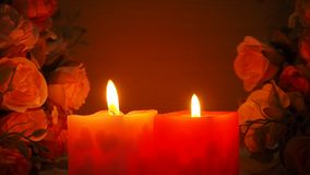 Two flaming candles with roses stock video footage