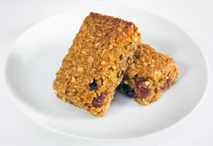 Two flapjacks stacked together on a plate. Delicious oaty cherry and raisin flapjacks stacked together on a plate, on a background of a white tablecloth Royalty Free Stock Photos