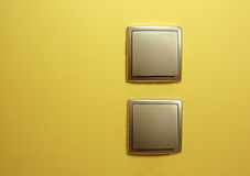 Two flat silver power switch, one below the other on the yellow Royalty Free Stock Photo