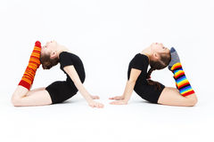 Two flexible teen girls doing gymnastics exercises on a white Stock Photography