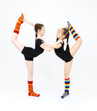 Two flexible teen girls doing gymnastics exercises on a white Royalty Free Stock Image