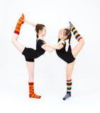 Two flexible teen girls doing gymnastics exercises on a white Royalty Free Stock Image
