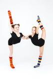 Two flexible teen girls doing gymnastics exercises on a white Royalty Free Stock Photo