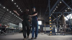 Two flight engineers walking through a hangar