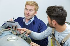 Two flight engineers working on airplane royalty free stock image