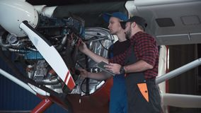Two flight mechanics doing a pre flight check. Or maintenance on a small single engine aircraft in a hangar in a close up view of them working on the engine stock video footage