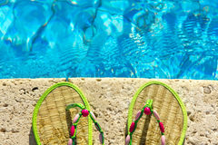 Two flip flops near swimming pool Stock Images