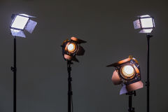 Two floodlights with halogen lamps and Fresnel lens and two led lighting device. Shooting in the interior on a gray background.  Royalty Free Stock Images