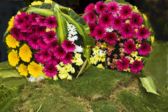 Two Flower Boquets. Beautifully created two flower bouquets placed on grass mound Royalty Free Stock Image