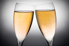 Two flutes of champagne with gold bubbles Stock Image