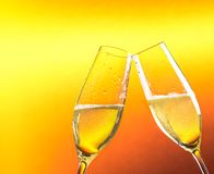 Two flutes of champagne with golden bubbles and space for text Royalty Free Stock Images