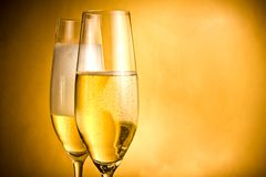 Two flutes of champagne with golden bubbles and white foam Stock Photo