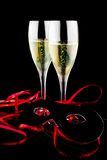 Two flutes with champagne near a carnival mask Royalty Free Stock Images
