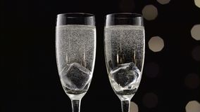 Two flutes of champagne with transparent pieces of ice on the bottom.Bokeh blinking black background. Close up. Two flutes of champagne with slices of stock video footage