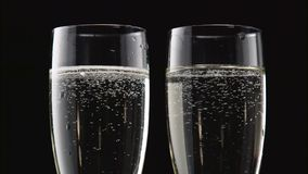Two flutes of chilled sparkling wine. Bokeh blinking black background. Close up. Two flutes of chilled sparkling wine with a rotating bubbles forming inside the stock video footage