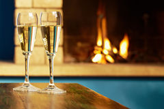 Two flutes filled with champagne near fireplace Stock Images