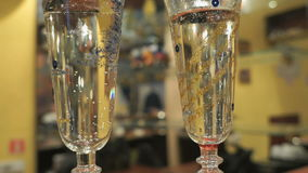 Two flutes with sparkling wine over holiday. Couple of champagne glasses on table close-up stock video