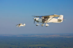Two Flying Planes. Two identical white ultralight airplanes in flight Stock Photo