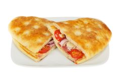 Two focaccia sandwiches. Toasted cheese,onion, ham and tomata focaccia sandwiches on a plate isolated against white stock photography