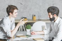 Two focused males working on project together. In modern office at desk with laptop, coffee cup, supplies and other items. Teamwork, meeting, togetherness Royalty Free Stock Image