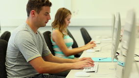 Two focused students working in computer room. At the university stock video footage