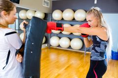 Two focused young women training boxing in fitness gym center royalty free stock photos