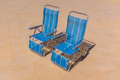 Two foldable nylon stripe deck chairs in the sunshine. Two blue nylon stripe foldable recliner deck chairs in an upright position with no body sitting on them royalty free stock photography