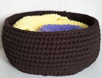 Two folded knitted blankets in the brown basket on the white table stock photo