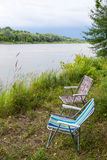 Two folding chairs on nature, on the banks of the river Stock Photo
