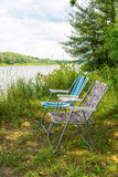Two folding chairs on nature, on the banks of the river Royalty Free Stock Images