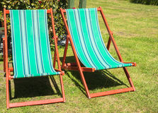 Two folding deck chairs in garden. Royalty Free Stock Photos