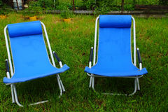Two folding deck chairs on the grass. Two folding deck chairs on the green grass royalty free stock images
