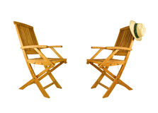 Two folding teak wood deck chair. With sun hat on a white background royalty free stock photos